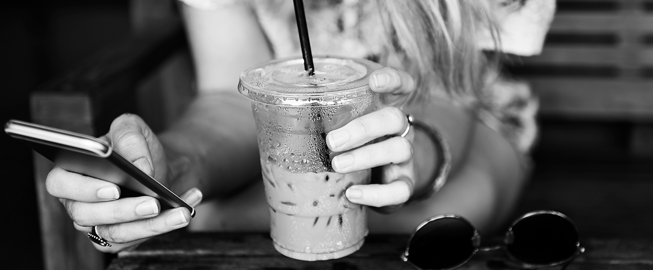 Young woman holding mobile phone at a coffee shop.