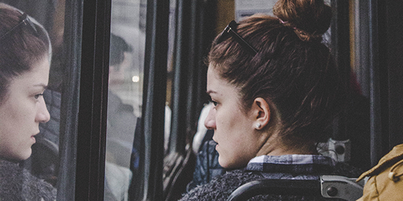 Woman looking out window of bus, melancholy.