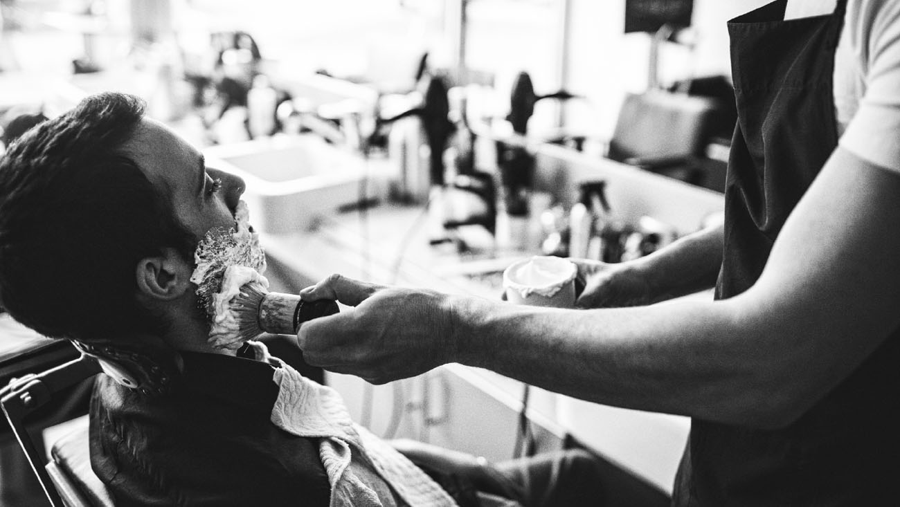 A man getting a shave at the barber shop.