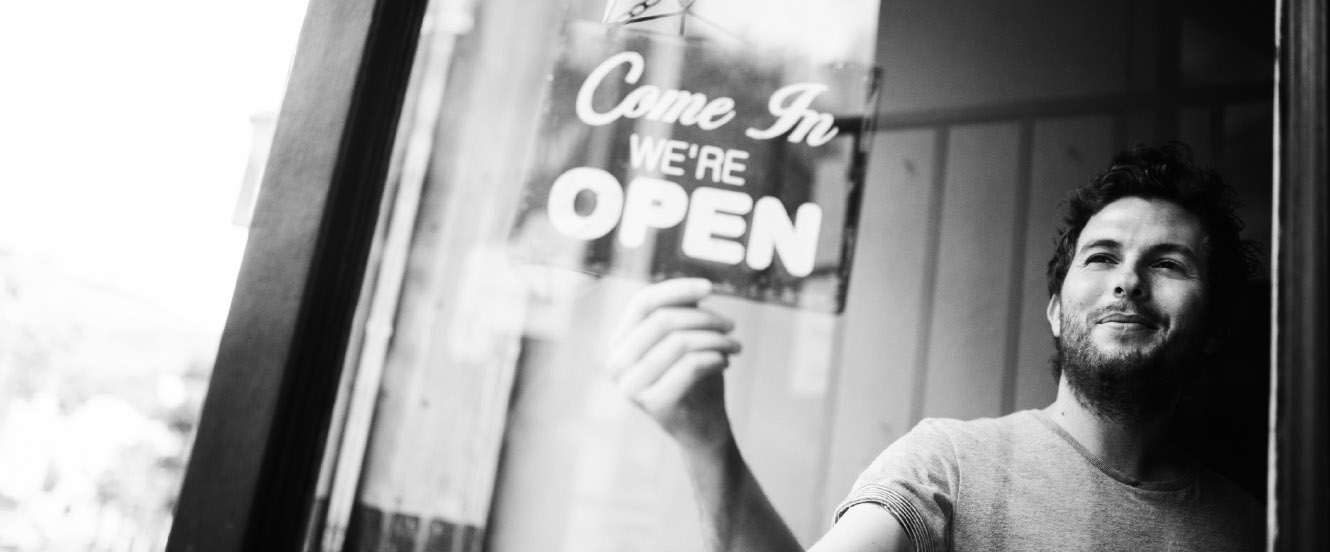 A man places an 'Open' sign in the window of his business.
