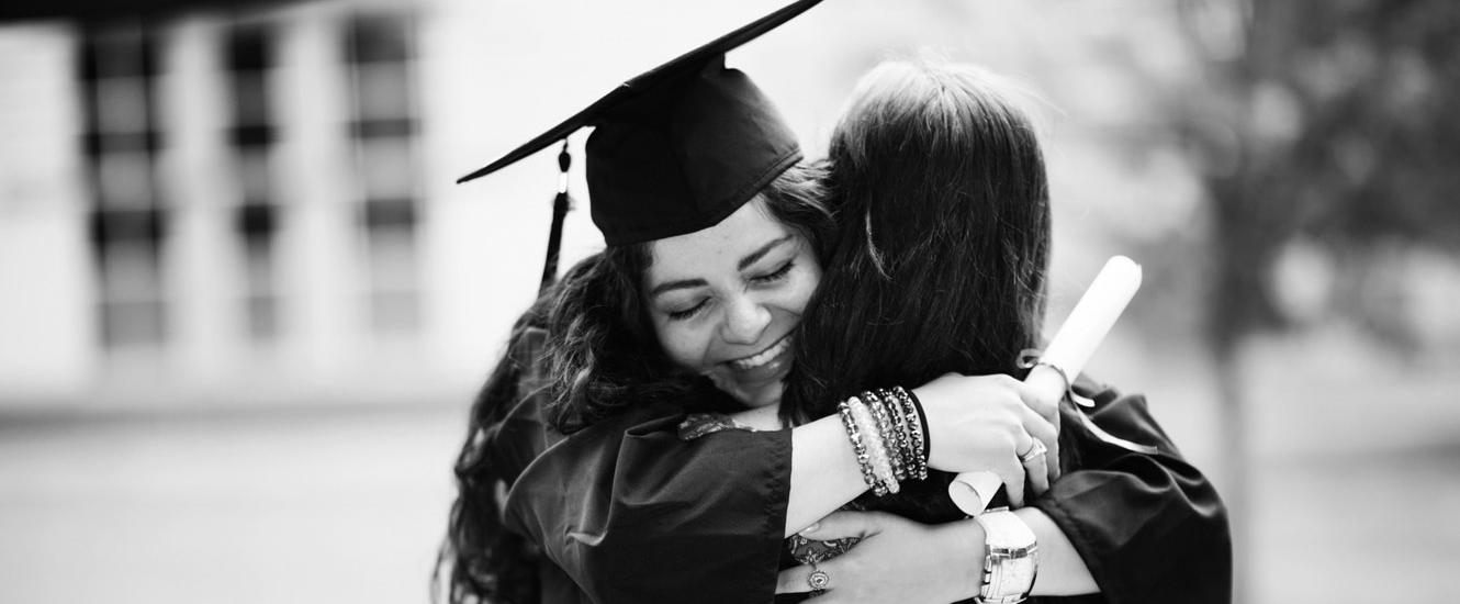 Female college student hugs her mom on graduation day.