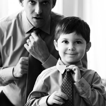 Father and son tying ties together.