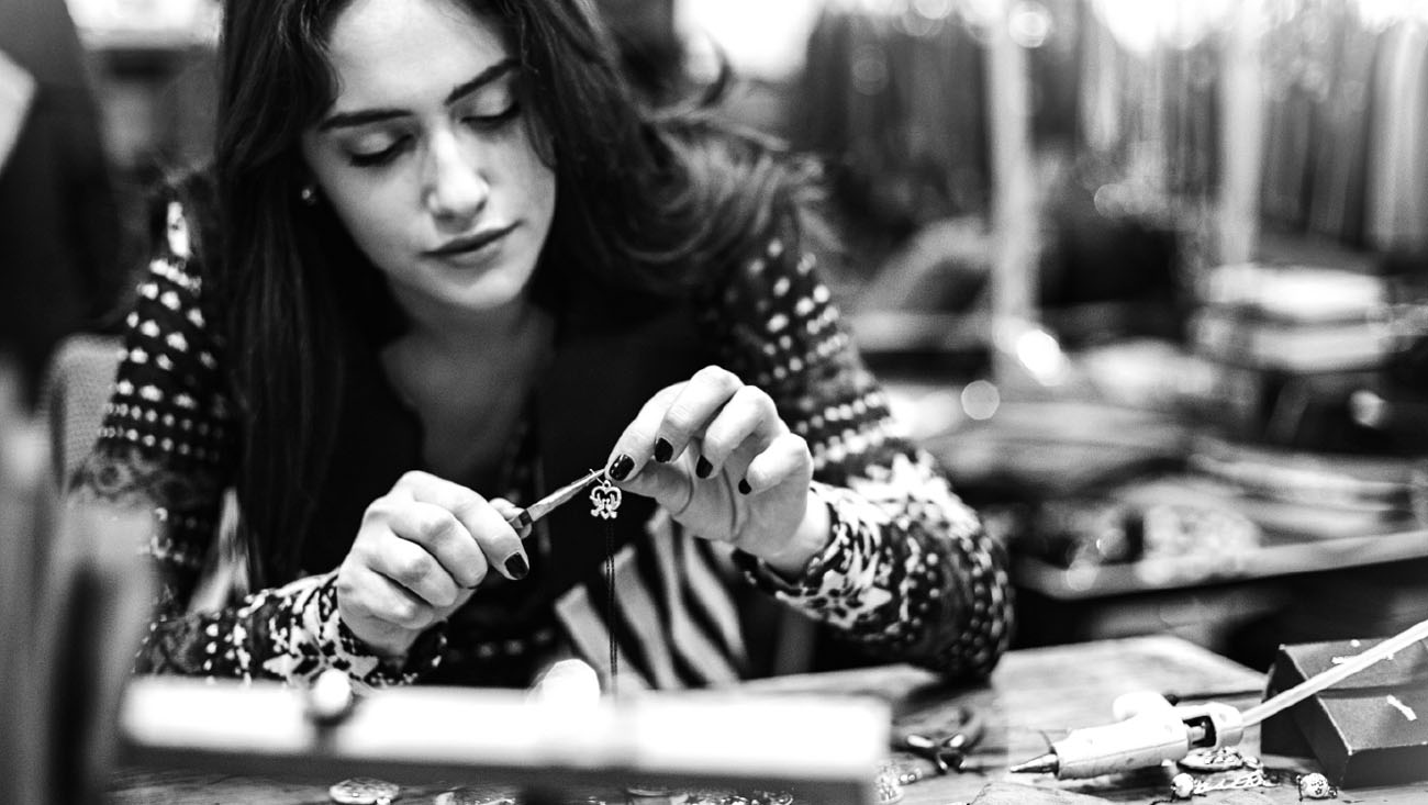 A young woman making jewelry.