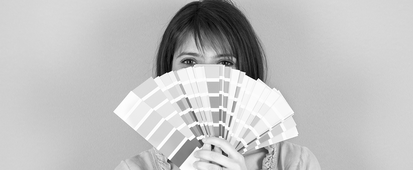 Woman holding up a fan of paint samples in front of her face.