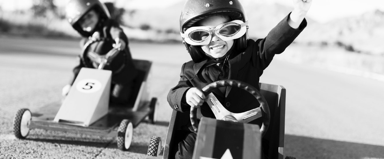 Two boys drive small race cars around.