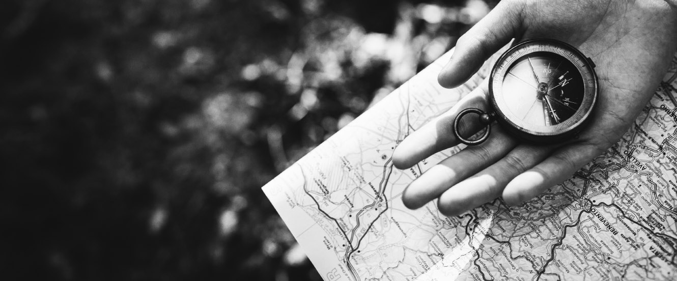 A hand holding a compass on top of a map.