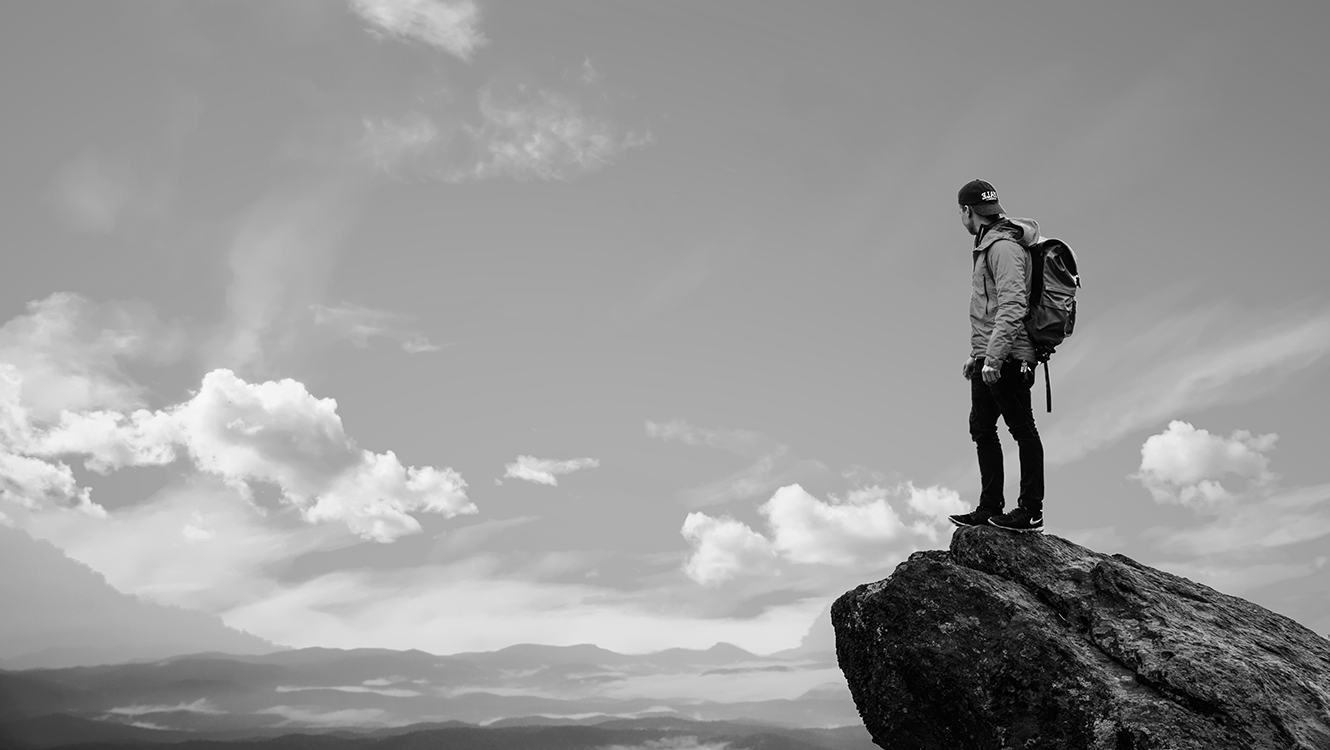 Guy with backpack standing on mountain top.